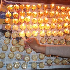 a photograph of a hand lighting many small votive candles set on newspapers on the ground in Nepal as part of a religious ceremony