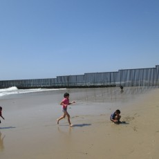 Children and U.S. Mexico Border Fence, from Mexico, a 31-Year Journey, 2013, Inkjet Print on Hahnemule Fine Art Paper, 24 x 20 inches, edition of 9.   These children could care less about the border fence behind them, jutting out into the surf of the Pacific Ocean, separating Mexico and the United States.  When I visited here I was very moved and shocked to see the huge extent of security, with helicopters, watch towers, search lights, and uniformed border patrol officers patrolling the land just on the other side of the fence.