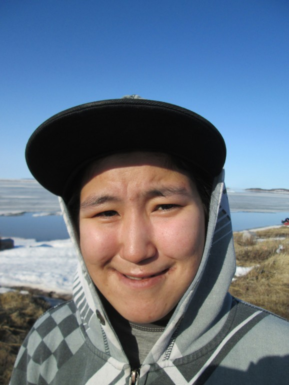 "Kayla, Kugluktuk, Nunavut, Canada, from The Far North, Portrait of the Arctic, 2014, Inkjet Print on Hahnemule Fine Art Paper, 24 x 20 Inches, Edition of 9.  I met Kayla while I was photographing on the beach of the Arctic Ocean. The ocean was still frozen there in mid-May. Kayla is a skilled artisan, a carver.  Her father is also a carver. Kugluktuk, almost half-way from Spokane to the North Pole, is in Canada's newest and northern-most territory, Nunavut. Nunavut, formed in 1999, means ""our land"" in the native language. Kugluktuk has a population of 1400. The nearest hospital is a two hour flight away to Yellowknife, Northwest Territories. The people of Kugluktuk depend on each other for survival in a harsh environment. The Hunter Trapper Organization of Kugluktuk shares extra whale and seal meat with community members after harvests."