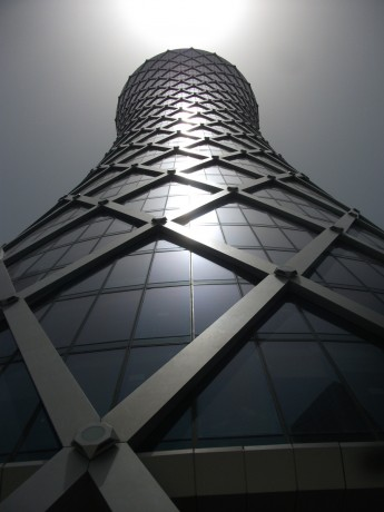 Skyscraper Light, Doha, Qatar, 2011, Inkjet Print on Hahnemule Fine Art Paper, 20 x 24 inches, edition of 10.   One of the many beautiful new skyscrapers in Doha, the capital of Qatar.  This building appears to have a light shooting from its top floor, in a solar abstraction, almost as if it has become a kind of gargantuan flashlight of many hundreds of feet height.  It appears to not be real.  But it is real.  Qatar borders Saudi Arabia and the Persian Gulf and has the highest per-capita income of any nation in the world.